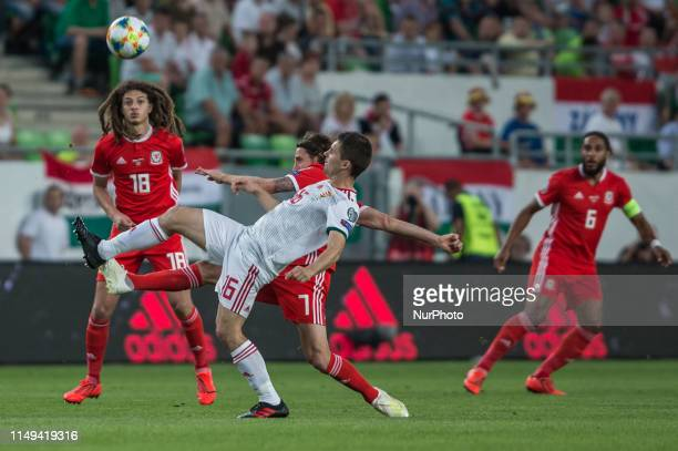 Joe Allen of Wales competes for the ball with Mate Pátkai of Hungary during the Hungary and Wales European Qualifier match at Groupama stadium on...
