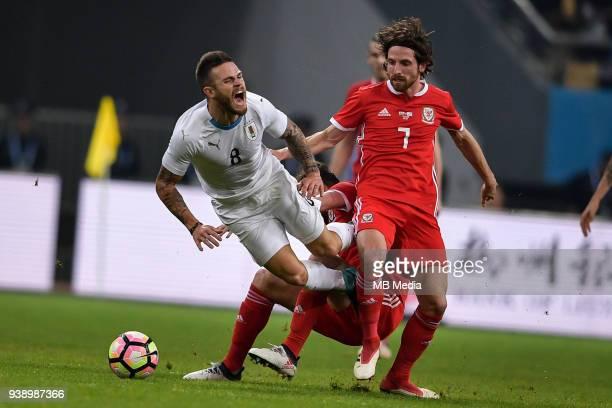 Joe Allen right of Wales national football team kicks the ball to make a pass against Nahitan Nandez of Uruguay national football team in their final...