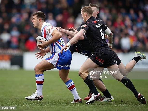 Joe Arundel of Wakefield Wildcats under pressure from Kevin Brown of Widnes Vikings during the First Utility Super League Round One match between...
