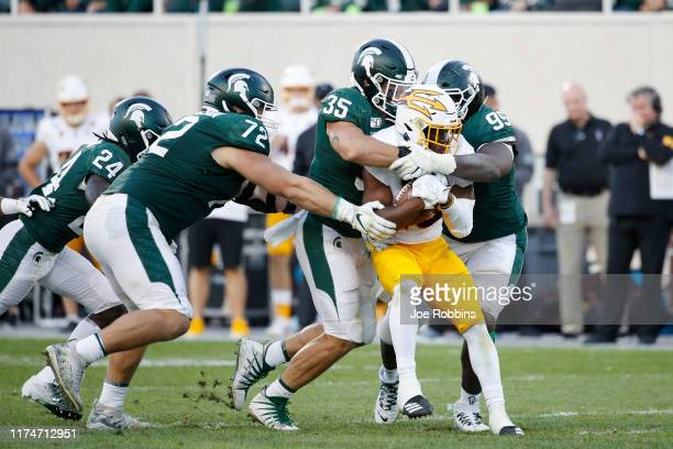 Joe Bachie and Raequan Williams of the Michigan State Spartans tackle Eno Benjamin of the Arizona State Sun Devils in the second half of the game at...