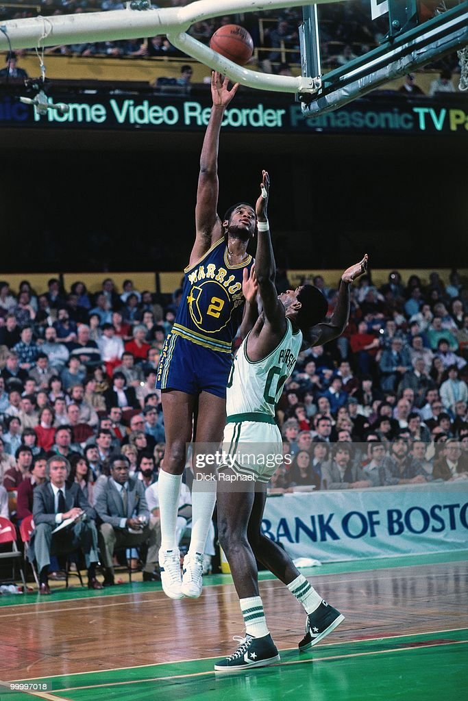Joe Barry Carroll #2 of the Golden State Warriors shoots a layup against Robert Parish #00 of the Boston Celtics during a game played in 1983 at the Boston Garden in Boston, Massachusetts.