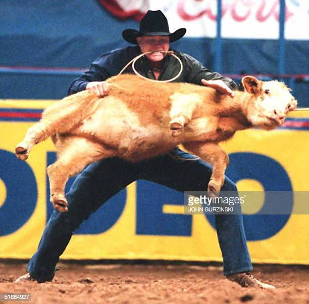 Joe Beaver of Huntsville Texas lifts a calf during the calf roping event 04 December in Las Vegas Nevada during of the National Finals Rodeo Beaver...
