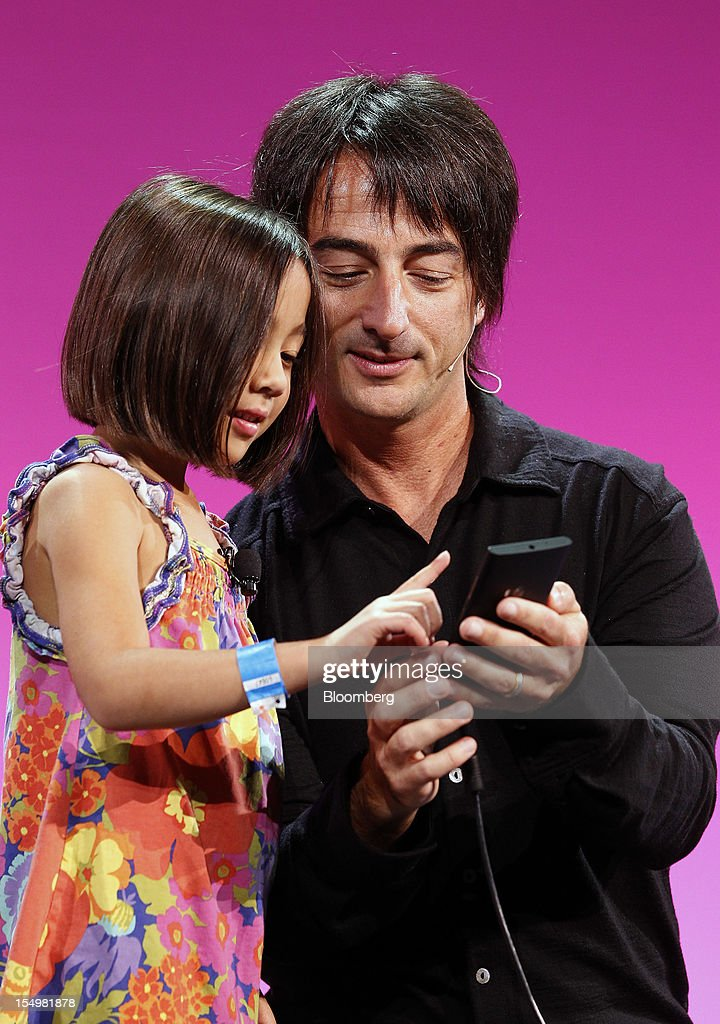 Joe Belfiore, vice president at Microsoft Corp., right, and his daughter Piper introduce the Kid's Corner feature of Windows Phone 8 software in San Francisco, California, U.S., on Monday, Oct. 29, 2012. Microsoft Corp. unveiled a new version of its software for smartphones today, redoubling an effort to regain market share lost to Apple Inc. and Google Inc. Photographer: Tony Avelar/Bloomberg via Getty Images