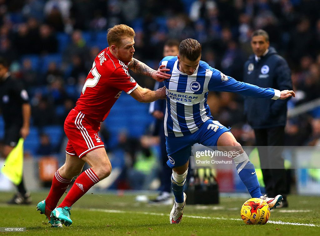 Joe Bennett of Brighton (R) is fouled by Forest's Chris Burke during the Sky Bet Championship match between Brighton & Hove Albion and Nottingham Forest at The Amex Stadium on February 07, 2015 in Brighton, England.