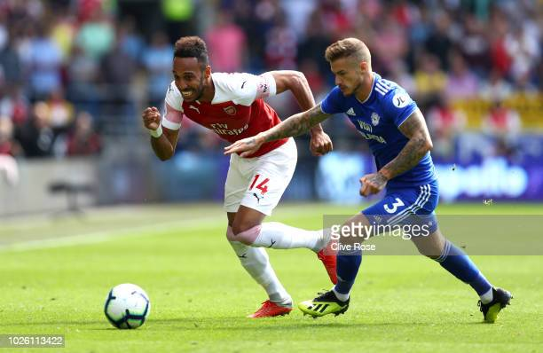 Joe Bennett of Cardiff City battles with PierreEmerick Aubameyang of Arsenal during the Premier League match between Cardiff City and Arsenal FC at...