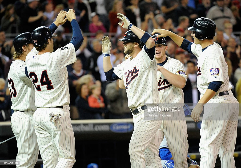 Joe Benson #63, Trevor Plouffe #24, Rene Tosoni #23, Chris Parmelee #64 and Danny Valencia #19 of the Minnesota Twins celebrate a grand slam home run by Tosoni in the sixth inning against the Kansas City Royals on September 27, 2011 at Target Field in Minneapolis, Minnesota.