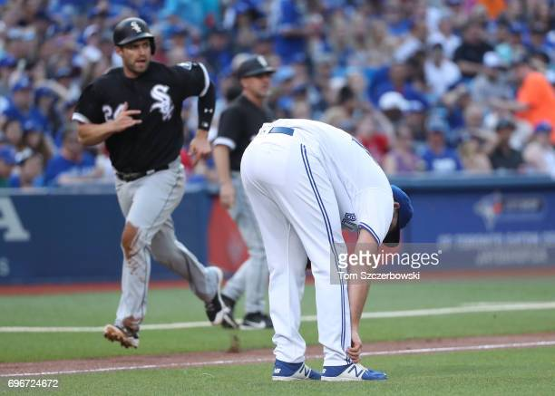Joe Biagini of the Toronto Blue Jays reacts after making a throwing error allowing Matt Davidson of the Chicago White Sox to score in the first...