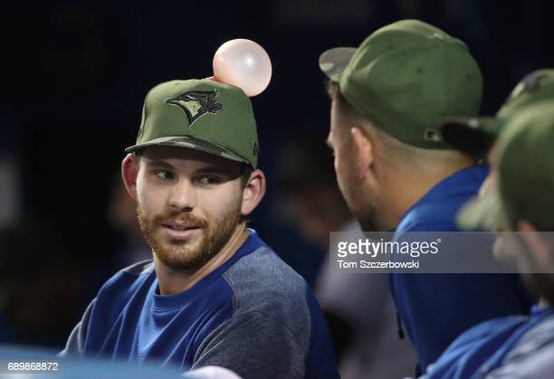 Joe Biagini of the Toronto Blue Jays talks to Marco Estrada while unaware of the bubble on his hat during MLB game action against the Cincinnati Reds...