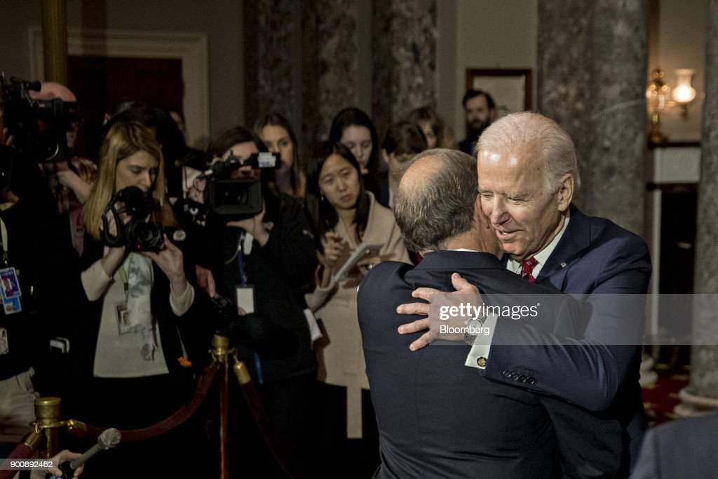 Joe Biden, former U.S. Vice President, right, hugs Senator Doug Jones, a Democrat from Alabama, after being sworn-in by U.S. Vice President Mike Pence, not pictured, during a mock swear-in ceremony in the Old Senate Chamber of the U.S. Capitol in Washington, D.C, U.S., on Wednesday, Jan. 3, 2018. Jones won a special election over Roy Moore to fill out the rest of the unexpired term of Attorney General Jeff Sessions. Photographer: Andrew Harrer/Bloomberg via Getty Images
