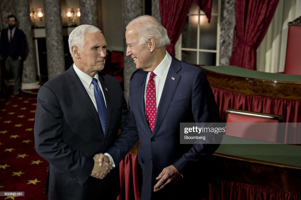 Joe Biden, former U.S. Vice President, right, shakes hands with U.S. Vice President Mike Pence after swearing-in Senator Doug Jones, a Democrat from Alabama, not pictured, during a mock swear-in ceremony in the Old Senate Chamber of the U.S. Capitol in Washington, D.C, U.S., on Wednesday, Jan. 3, 2018. Jones won a special election over Roy Moore to fill out the rest of the unexpired term of Attorney General Jeff Sessions. Photographer: Andrew Harrer/Bloomberg via Getty Images