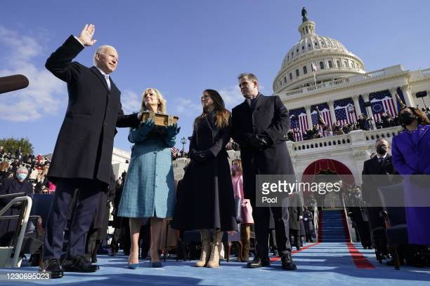 Joe Biden is sworn in as the 46th president of the United States by Chief Justice John Roberts as Jill Biden holds the Bible and their children...