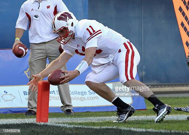 Joe Brennan of the Wisconsin Badgers gets the ball inside the pylon to score a touchdown against the Northern Illinois Huskies at Soldier Field on...