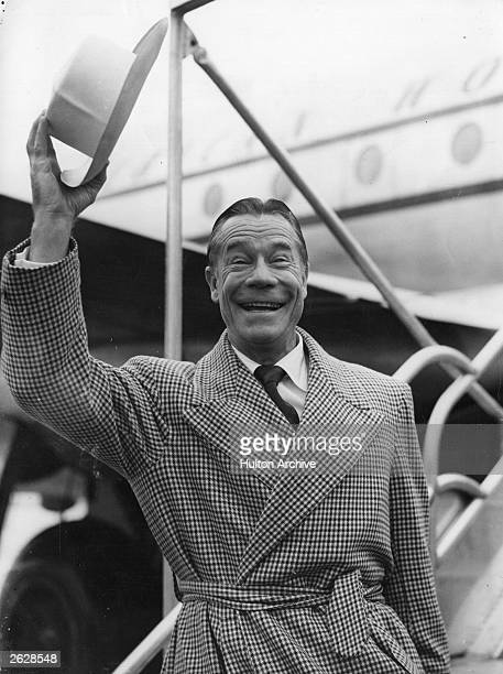Joe Brown American film actor standing beside an aeroplane waving his hat