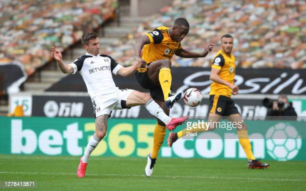 Joe Bryan of Fulham battles for possession with Willy Boly of Wolverhampton Wanderers during the Premier League match between Wolverhampton Wanderers...