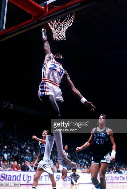 Joe Bryant of the Philadelphia 76ers goes up for slam dunk against the San Antonio Spurs during an NBA basketball game circa 1977 at The Spectrum in...