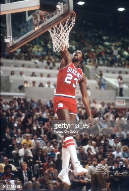 Joe Bryant of the Philadelphia 76ers slam dunks against the New Jersey Nets during an NBA basketball game circa 1979 at the Rutgers Athletic Center...