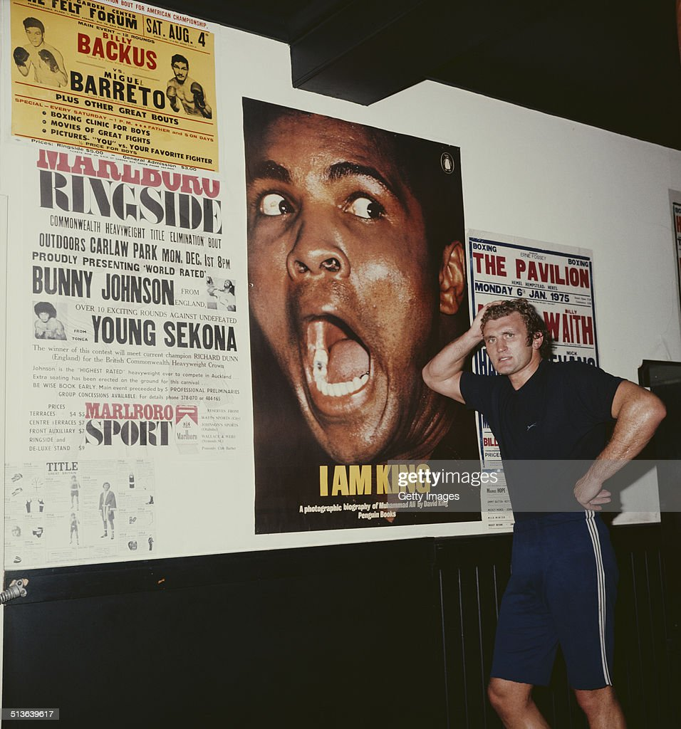 Joe Bugner of Great Britain, the two time British and Commonwealth heavyweight and three-time European heavyweight champion poses next to a poster of Muhammad Ali during training for their fight on 1st May 1975 in London, Great Britain.