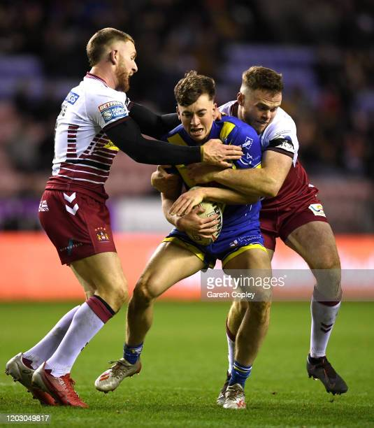 Joe Burgess and Jackson Hastings of Wigan tackle Matthew Ashton of Warrington during the Betfred Super League match between Wigan Warriors and...
