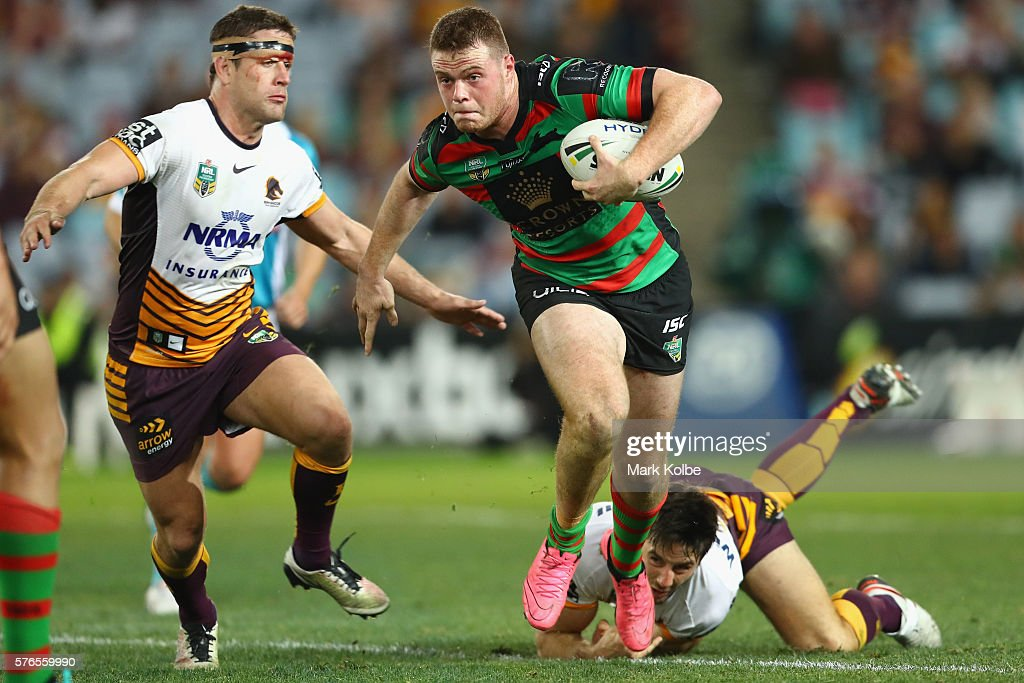 Joe Burgess of the Rabbitohs beats the tackle of Andrew McCullough (L) and Ben Hunt (R) of the Broncos during the round 19 NRL match between the South Sydney Rabbitohs and the Brisbane Broncos at ANZ Stadium on July 16, 2016 in Sydney, Australia.