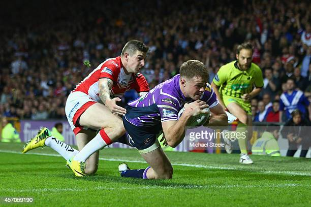Joe Burgess of Wigan scores the opening try despite the attentions of Mark Percival of St Helens during the First Utility Super League Grand Final...