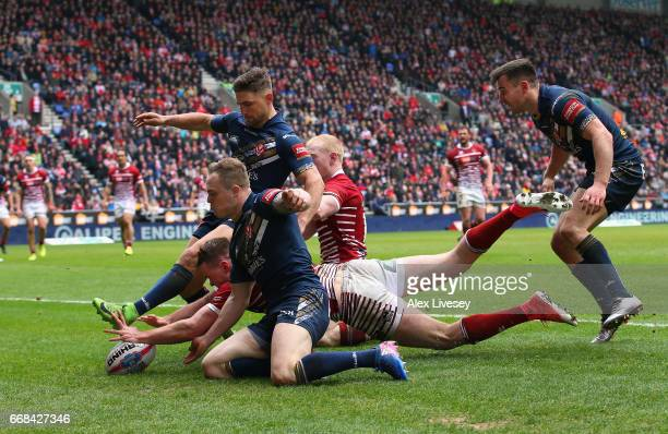 Joe Burgess of Wigan Warriors dives through to score the opening try during the Betfred Super League match between Wigan Warriors and St Helens at DW...