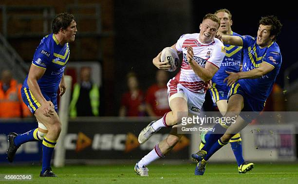 Joe Burgess of Wigan Warriors gets past Ben Harrison and Stefan Ratchford of Warrington Wolves during the First Utility Super League Qualifying...