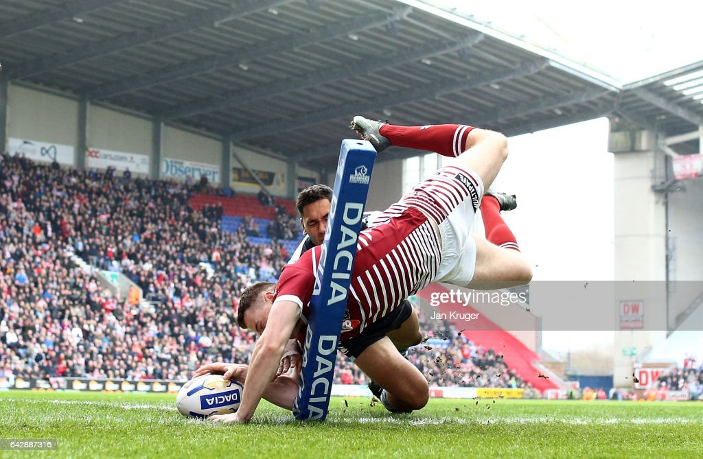 Joe Burgess of Wigan Warriors goes over for the opening try under pressure from Jesse Raimen of Cronulla-Sutherland Sharks during the Dacia World Club Challenge match between Wigan Warriors and Cronulla-Sutherland Sharks at DW Stadium on February 19, 2017 in Wigan, England.