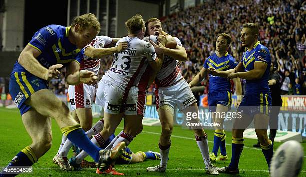 Joe Burgess of Wigan Warriors is mobbed by teammates after scoring the winning try past during the First Utility Super League Qualifying Semi-Final...
