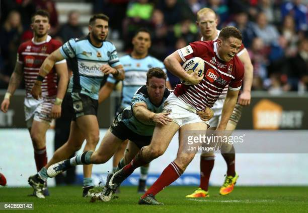 Joe Burgess of Wigan Warriors is tackled by James Maloney of CronullaSutherland Sharks during the Dacia World Club Challenge match between Wigan...