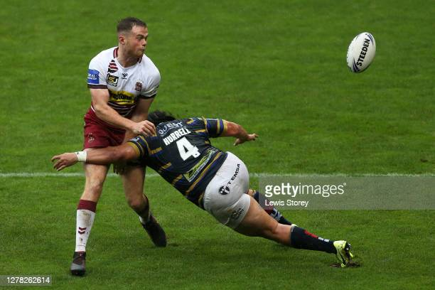Joe Burgess of Wigan Warriors is tackled by Konrad Hurrell of Leeds Rhinos during the Coral Challenge Cup Semi-Final match between Leeds Rhinos and...