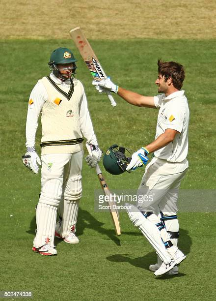 Joe Burns of Australia celebrates as he reaches his century as Usman Khawaja looks on during day one of the Second Test match between Australia and...