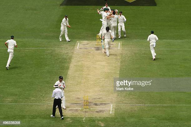 Joe Burns of Australia celebrates with team mates after taking the catch off the bowling of Mitchell Johnson of Australia to dismiss James Neesham of...