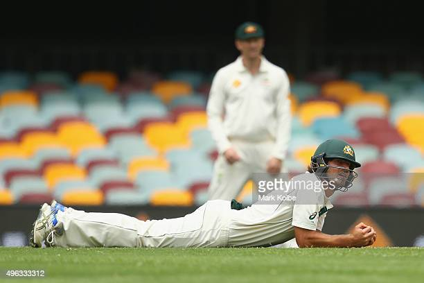 Joe Burns of Australia looks at the umpire after diving to catch a ball at short leg during day five of the First Test match between Australia and...