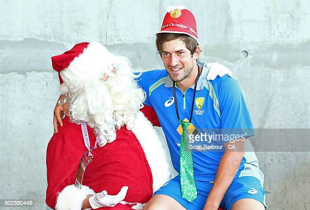 Joe Burns of Australia sits on Santa's lap during the MILO in2CRICKET session at the Melbourne Cricket Ground on December 24 2015 in Melbourne...