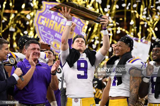 Joe Burrow head coach Ed Oregon and Grant Delpit of the LSU Tigers receive the trophy after defeating the Clemson Tigers during the College Football...