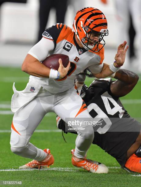 Joe Burrow of the Cincinnati Bengals is sacked by Adrian Clayborn of the Cleveland Browns during the first quarter at FirstEnergy Stadium on...