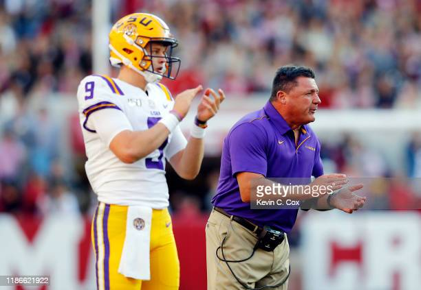 Joe Burrow of the LSU Tigers and head coach Ed Orgeron react during the first half against the Alabama Crimson Tide in the game at BryantDenny...