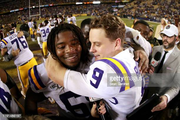 Joe Burrow of the LSU Tigers celebrates with Damien Lewis of the LSU Tigers after his team defeated the Texas A&M Aggies at Tiger Stadium on November...
