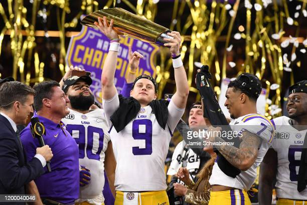 Joe Burrow of the LSU Tigers holds up the trophy after defeating the Clemson Tigers during the College Football Playoff National Championship held at...