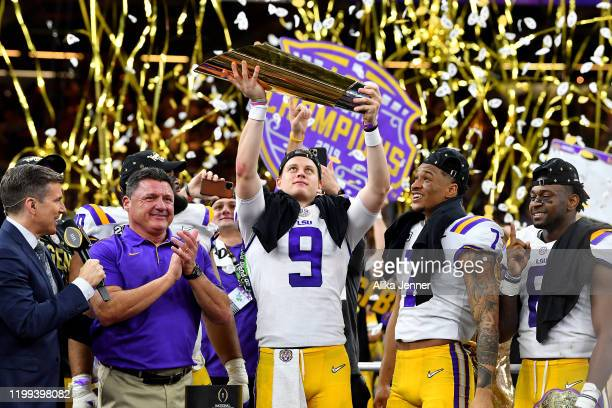 Joe Burrow of the LSU Tigers raises the National Championship Trophy with Ed Orgeron Grant Delpit and Patrick Queen after the College Football...