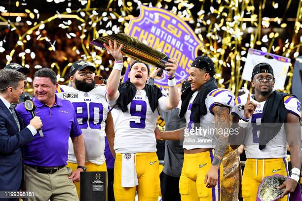 Joe Burrow of the LSU Tigers raises the National Championship Trophy with Ed Orgeron Grant Delpit Patrick Queen and Rashard Lawrence after the...