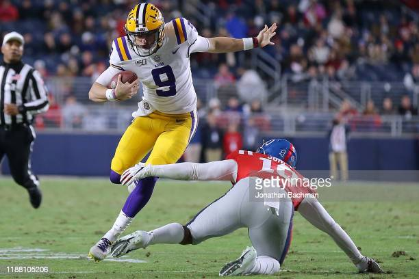 Joe Burrow of the LSU Tigers runs with the ball as Jacquez Jones of the Mississippi Rebels defends during the first half of a game at VaughtHemingway...