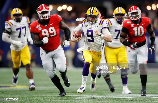 Joe Burrow of the LSU Tigers runs with the ball in the first half against the Georgia Bulldogs during the SEC Championship game at MercedesBenz...