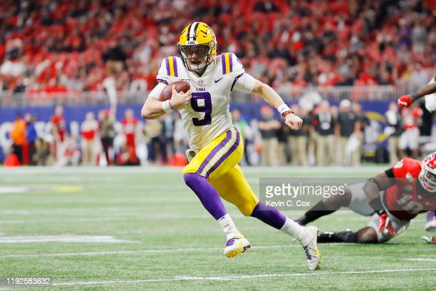 Joe Burrow of the LSU Tigers runs with the ball in the second half against the Georgia Bulldogs during the SEC Championship game at MercedesBenz...