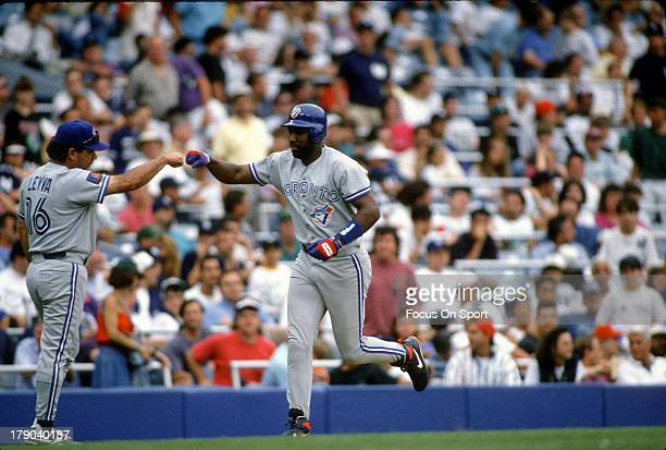 Joe Carter of the Toronto Blue Jays is congratulated by third base coach Nick Leyva after Cater hit a home run during an Major League Baseball game...