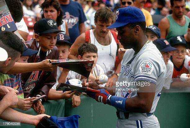 Joe Carter of the Toronto Blue Jays signs autographs for fans prior to the start of a Major League Baseball game against the Boston Red Sox circa...