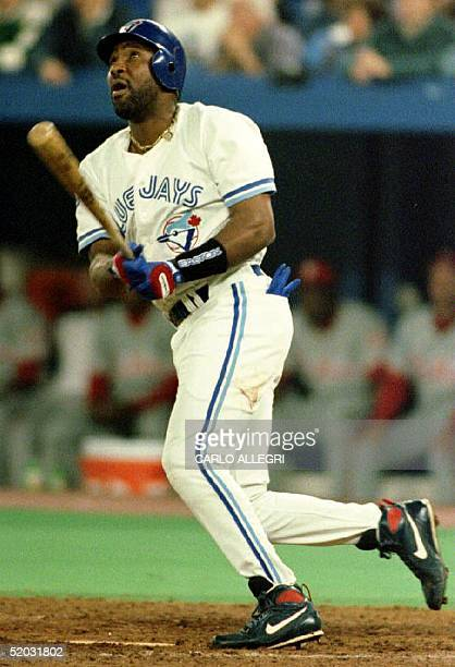 Joe Carter of the Toronto Blue Jays watches the flight of his threerun home run in the bottom of the ninth inning to win Game 6 of the 1993 World...