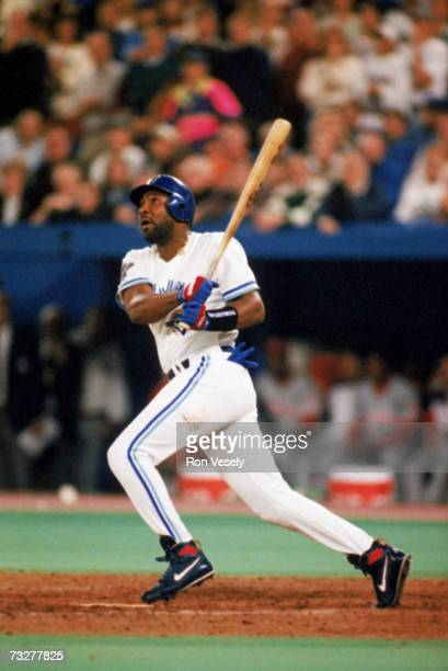 Joe Carter of the Toronto Blue Jays watches the flight of his threerun home run in the bottom of the ninth inning to win game six of the 1993 World...
