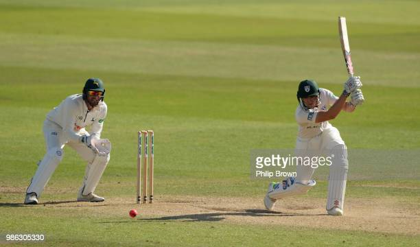 Joe Clarke of Worcestershire hits out watched by Riki Wessels of Nottinghamshire during the Specsavers County Championship Division One match between...