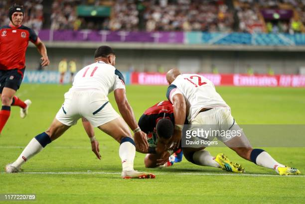 Joe Cokanasiga of England goes over to score his team's fourth try under a challenge from Paul Lasike and Martin Iosefo of USA during the Rugby World...